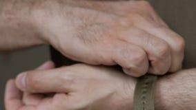 Primer de las manos de hombres en ropa de color caqui, llevadas en la mu?eca del reloj del buceador en la correa de nylon almacen de video