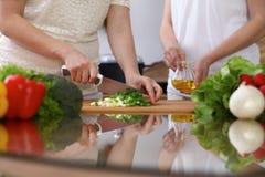 Primer de las manos humanas que cocinan en cocina Madre e hija o hembra dos que corta la cebolla verde para la ensalada Comida sa imagenes de archivo