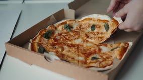 Primer de las manos de la gente que toman la pizza de las rebanadas de la caja abierta de la entrega de la comida Servicio sabros almacen de video