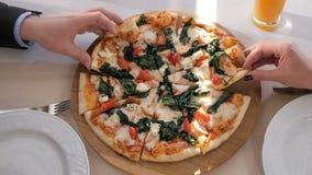 Primer de las manos de la gente tomar pedazos de pizza