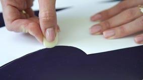 Primer de las manos de la mujer joven que dibujan la plantilla en tela con tiza de la adaptación metrajes