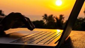 Primer de las manos masculinas de la silueta que mecanografían en el ordenador portátil en la puesta del sol hermosa fotos de archivo libres de regalías