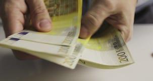Primer de las manos masculinas que cuentan doscientas cuentas euro almacen de video