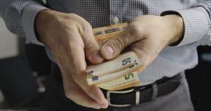 Primer de las manos masculinas que cuentan un paquete de cincuenta cuentas euro metrajes