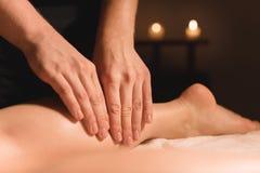 Primer de las manos masculinas que hacen el masaje del becerro de piernas femeninas en un cuarto oscuro con las velas en el fondo foto de archivo libre de regalías
