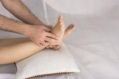 Primer de las manos masculinas que hacen masaje del pie imagen de archivo