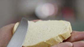 Primer de las manos masculinas que separan la mantequilla en el pan en cocina en la c?mara lenta metrajes