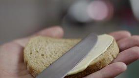 Primer de las manos masculinas que separan lentamente la mantequilla en el pan marr?n de la prohibici?n en cocina almacen de video
