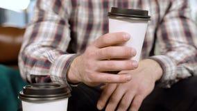Primer de las manos masculinas que sostienen un vidrio de café almacen de metraje de vídeo