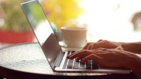 Primer de las manos masculinas usando el ordenador portátil en el café almacen de metraje de vídeo