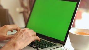 Primer de las manos masculinas usando el ordenador portátil en el café con la pantalla verde almacen de metraje de vídeo