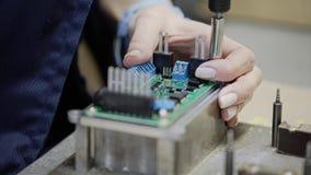 Primer de las manos de las mujeres en la fábrica durante el montaje del dispositivo electrónico Primer de los componentes para la metrajes