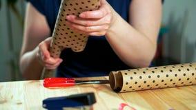 Primer de las manos de las mujeres que sostienen el papel de embalaje del arte almacen de video