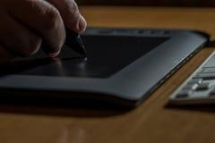 Primer de las manos que dibujan en la tableta gráfica foto de archivo