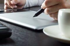Primer de las manos que dibujan en la tableta gráfica Fotos de archivo