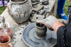 Primer de las manos que hacen la cerámica de la arcilla en una rueda Fotos de archivo libres de regalías