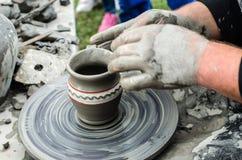 Primer de las manos que hacen la cerámica de la arcilla en una rueda Imagen de archivo libre de regalías