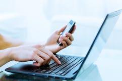 Primer de las manos que mecanografían en el ordenador portátil mientras que usa un teléfono celular imagenes de archivo