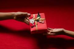 Primer de las manos que sostienen la caja de regalo en fondo rojo Fotografía de archivo libre de regalías