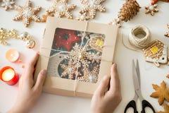 Primer de las manos que sostienen una caja festiva con las galletas de la Navidad Fotografía de archivo libre de regalías