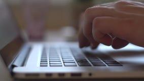 Primer de las manos que trabajan y que mecanografían en un teclado del ordenador portátil con llaves negras y una pantalla ligera almacen de metraje de vídeo