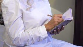 Primer de las manos de una mujer que hace notas en su cuaderno almacen de metraje de vídeo