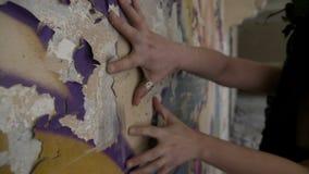 Primer de las manos y de los fingeres de la mujer que rasguñan una pared arruinada metrajes