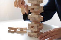 Primer de las mujeres que juegan al juego de la pila de los bloques de madera, concepto de crecimiento del negocio, jugando, ries imágenes de archivo libres de regalías