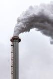Primer de las nubes de humo oscuras sucias de una alta chimenea industrial Fotos de archivo libres de regalías
