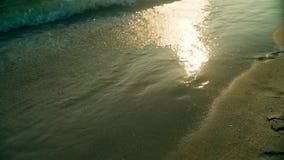 Primer de las ondas del mar que lavan en tierra a Sandy Beach en la cámara lenta en la puesta del sol metrajes
