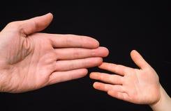 Primer de las palmas caucásicas pequeñas y grandes de la mano Foto de archivo libre de regalías