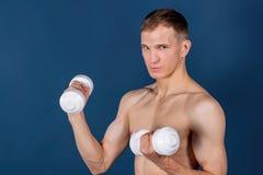 Primer de las pesas de gimnasia de elevación musculares de un hombre joven en fondo azul imagen de archivo libre de regalías