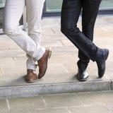 Primer de las piernas de dos hombres de negocios que se colocan afuera Foto de archivo libre de regalías