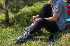 Primer de las piernas de la chica joven que llevan el zapato del patinaje sobre ruedas, al aire libre Imagenes de archivo