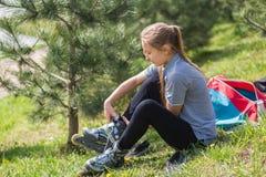 Primer de las piernas de la chica joven que llevan el zapato del patinaje sobre ruedas, al aire libre Imagen de archivo libre de regalías