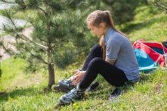 Primer de las piernas de la chica joven que llevan el zapato del patinaje sobre ruedas, al aire libre Fotos de archivo