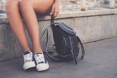 Primer de las piernas de la mujer en los gumshoes blancos Fotografía de archivo libre de regalías