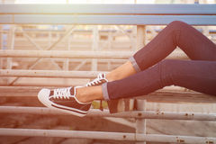 Primer de las piernas de la mujer en los gumshoes blancos Foto de archivo