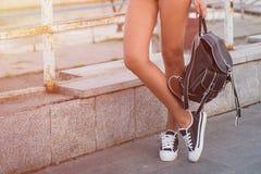 Primer de las piernas de la mujer en los gumshoes blancos Foto de archivo libre de regalías