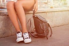 Primer de las piernas de la mujer en los gumshoes blancos Fotografía de archivo