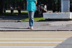 Primer de las piernas de la mujer joven que esperan en el paso de peatones Imagen de archivo libre de regalías
