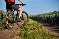 Primer de las piernas del hombre del ciclista con la bici de montaña en la trayectoria del campo verde en el campo Fotos de archivo