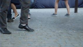 Primer de las piernas del ` s del bailarín La gente que baila el salto lindy baila en el pavimento del cuadrado del ` s de la ciu almacen de metraje de vídeo