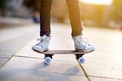 Primer de las piernas del skater Monopatín del montar a caballo del niño al aire libre Foto de archivo