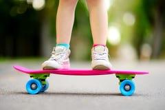 Primer de las piernas del skater Monopatín del montar a caballo del niño al aire libre Foto de archivo libre de regalías