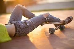 Primer de las piernas femeninas de moda que se relajan en un longboard Moda rasgada de los vaqueros Luz del sol al aire libre her imagenes de archivo
