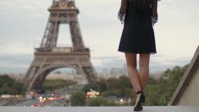 Primer de las piernas de la mujer delante de la torre Eiffel en París