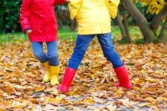 Primer de las piernas de los niños en las botas de goma que bailan y que caminan a través de las hojas de la caída fotos de archivo