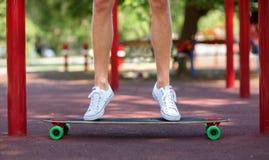 Primer de las piernas masculinas en un fondo natural Un individuo juguetón que salta en su longboard Deporte, al aire libre conce Foto de archivo libre de regalías