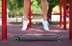 Primer de las piernas masculinas en un fondo natural Un individuo juguetón que salta en su longboard Deporte, al aire libre conce Fotografía de archivo libre de regalías